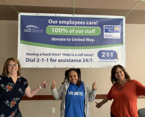 Three Tax Collector Employees standing under United Way banner.